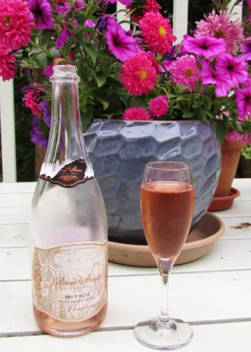 Anne Amie Vineyards 2011 Marilyn Brut Rosé - with a background of petunias and asters.