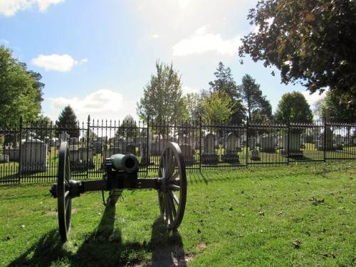 To the right of the cannon, there is a small tree. Behind that is a mausoleum believed to be near the site where the dais was placed for the cemetery dedication.