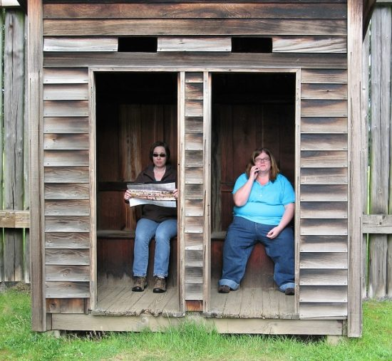 My cousin and I roleplaying in the double outhouse at Fort Vancouver. This one is a replica though