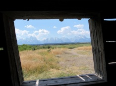 The view of the Grand Tetons through the window of the Cunningham Cabin